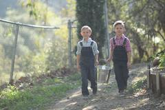 Stock Photo of kids working on the farm  with a pail