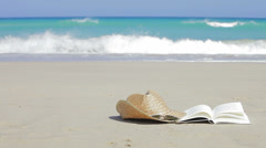 Book, sunglasses and straw hats on the beach. Relax concept - stock footage