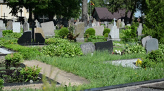 Rural cemetery graves tomb stones panorama and old woman Stock Footage