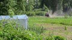 Small red tractor harrow the ground  near the homestead Stock Footage