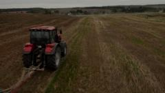 stock footage, aerial view flight over the tractor in the field - stock footage