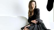 Beautiful female model posing on white sofa for photographer shoot Stock Footage