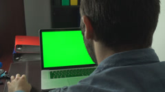 Young Business Man Browsing Trough Laptop WIth Green Screen, Back Shot Stock Footage