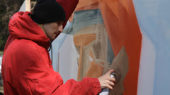 Graffiti artist works on his creation during the festival Stock Footage