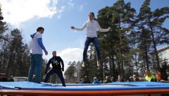 Young girl jumping on a trampoline during the festival Stock Footage