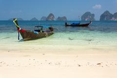 longtail boat on tropical shore - stock photo
