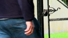 Man walks through an Iron gate, again. Stock Footage