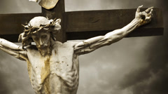 Crucifixion. Christian cross with Jesus Christ statue over stormy clouds - stock footage