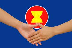 Asean economic community in businessman handshake Stock Photos