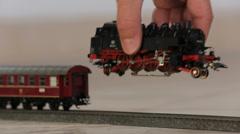 Puting toy train engine on track Stock Footage