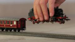 Kid puting toy train engine on track Stock Footage