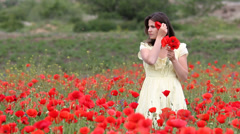 Romantic young lady arranging a poppy in the hair, blossom field, flower bouquet Stock Footage