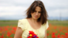 Beautiful young lady offer colored flower bouquet, poppy field, blur background Stock Footage
