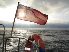 british maritime ensign flag boat and stormy sky - stock photo