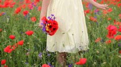 Gorgeous flowers spring bouquet in young lady hand in poppy field, romantic view - stock footage