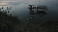 Desolated pontoon at twilight, sky reflect in serene lake Stock Footage