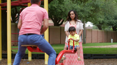 Mom and dad playing with their son on the see saw Stock Footage