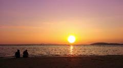 Sunset at tropical sea beach. Couple is enjoying the evening sun light. HD video Stock Footage