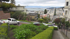 Lombard Street downhill switchback section route car pass district skyline USA  Stock Footage