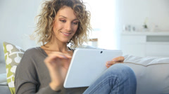 Smiling gorgeous woman websurfing on tablet Stock Footage