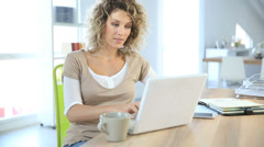Smiling woman sitting in front of laptop computer Stock Footage