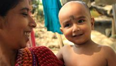 A closeup of an Indian village mother and her cute baby boy as he laughs Stock Footage