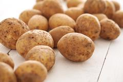 Rustic unpeeled potatoes on a table - stock photo