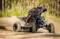 ATV racer takes a turn during a race. Stock Photos
