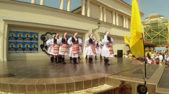 Folk dances in national costumes on stage in the open air in the city festival Stock Footage