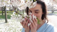 Woman in the park smells white flowers of a blossomed tree Stock Footage