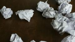 Person throwing a lot of crumpled paper on a desk, close-up, timelapse Stock Footage