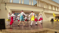 Folk round dances in national costumes on stage in the open air in the festival Stock Footage