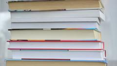 A stack of books on a desk indoors, close-up, camera moving up Stock Footage