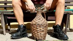 Legs of man sitting on a bench with carboy Stock Footage
