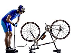 Cyclist repairing bicycle silhouette Stock Photos