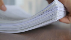 Person putting a stack of sheets on a desk at the office, close-up - stock footage