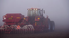 Stock video footage red tractor in a field, the morning mist - stock footage