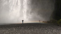 Girl running on a rainbow and getting showered in waterfall spray Stock Footage