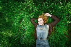 beautiful meditative young woman lying in the grass. summer, freedom concept. - stock photo