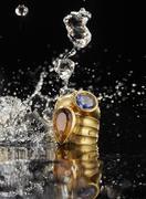 Golden ring with tanzanite and citrine, water splashing around - stock photo