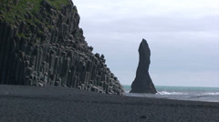 Pinnacle on sea and basalt column cliff on volcanic beach Stock Footage
