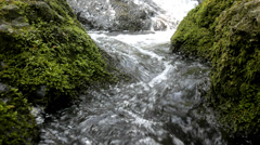 Cascade on small mountain stream, water is running on basalt rock down Stock Footage