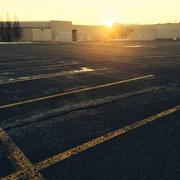 Empty parking near a shopping mall at sunset Stock Photos