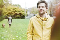 Portrait of smiling young man on grass verge - stock photo