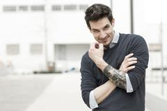 Portrait of smiling man with tattoo on his left arm Stock Photos