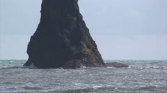 Pan right on sea stack pinnacle with waves crashing - stock footage