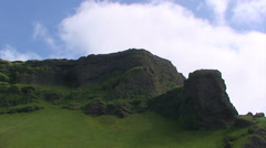 Fast clouds on basaltic rock cliff full of grass, time lapse Stock Footage