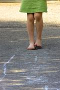 Little girl playing hopscotch with naked feet, partial view - stock photo