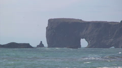 Sea cliffs in the distance with rock arch in seastack Stock Footage