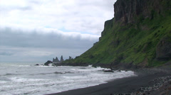 Sea stack pinnacles and cliff from volcanic beach Stock Footage